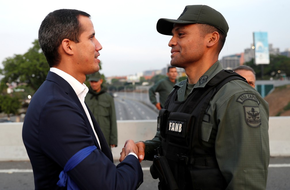 Juan Guaidó cumprimenta um militar perto de uma base aérea em Caracas — Foto: Carlos Garcia Rawlins/Reuters