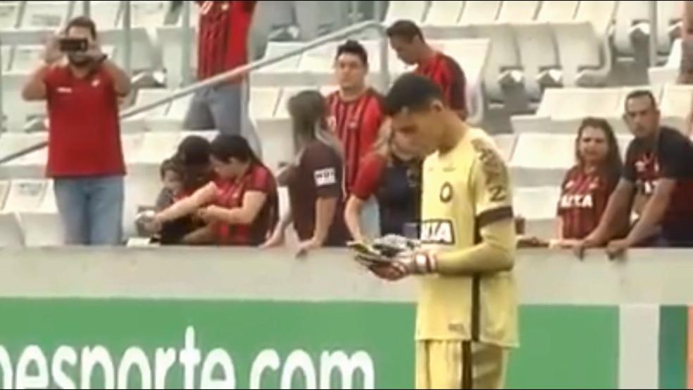 Goleiro Santos mexe no celular e solta o aparelho repentinamente. É possível ouvir o apito do árbitro (Foto: Reprodução)