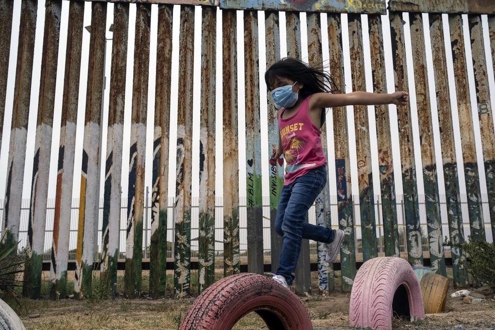 Menina usando máscara protetora contra a Covid-19 brinca perto da cerca na fronteira entre Estados Unidos e México, do lado mexicano, nesta quarta-feira (5). — Foto: Guillermo Arias/AFP