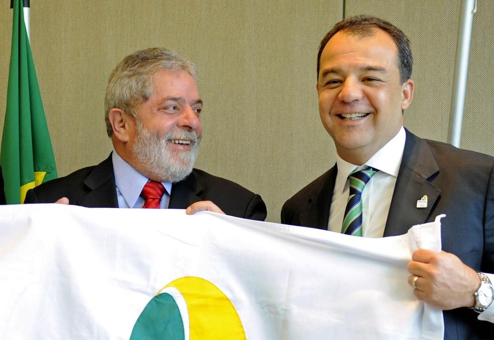 Luiz Inácio Lula da Silva (centro), então presidente, posa com uma bandeira da candidatura do Rio como sede da Olimpíada ao lado do então governador do Rio, Sérgio Cabral (dir.) em junho de 2009, em Genebra (Foto: Fabrice Coffrini/AFP/Arquivo)