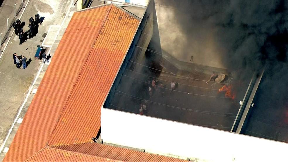 Homem joga colchão em direção ao fogo no cadeião de Pinheiros (Foto: Reprodução/TV Globo)