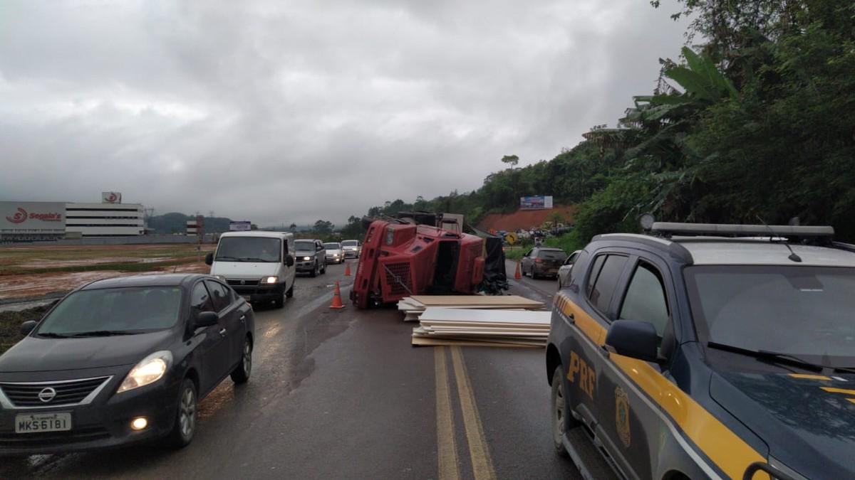 Caminhão carregado com placas de madeira tomba e deixa trânsito lento na BR-470, em Gaspar - G1