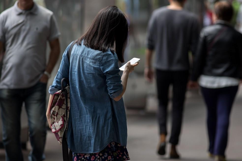 Mulher observa o celular na avenida Paulista, em São Paulo (Foto: Marcelo Brandt/G1)