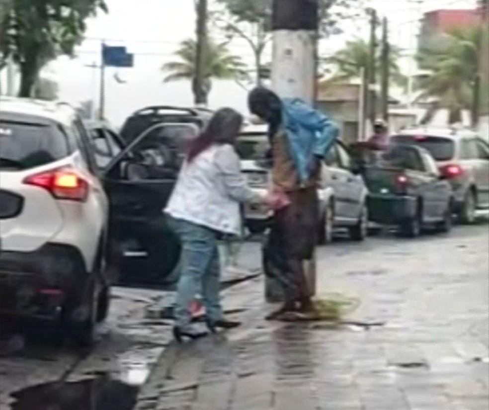 Mulher desce do carro, agasalha morador de rua na chuva e imagem comove internautas