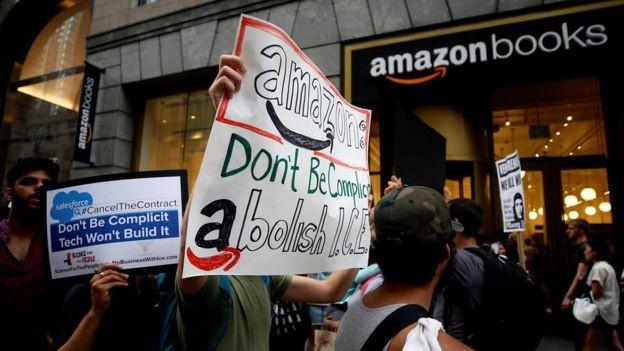 Cartazes de protesto pedem para Amazon 'não ser cúmplice' do serviço de imigração dos EUA (Foto: Getty Images via BBC News Brasil)
