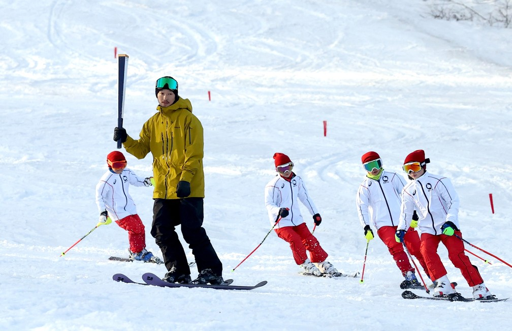 Ex-esquiador Sho Endo é acompanhado por crianças em ensaio do revezamento da tocha — Foto: Yasushi Kanno / Yomiuri / The Yomiuri Shimbun via AFP
