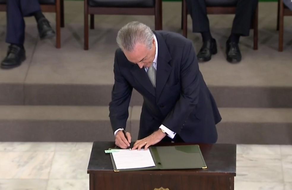 Temer assina documento durante cerimônia no Palácio do Planalto — Foto: Reprodução/NBR