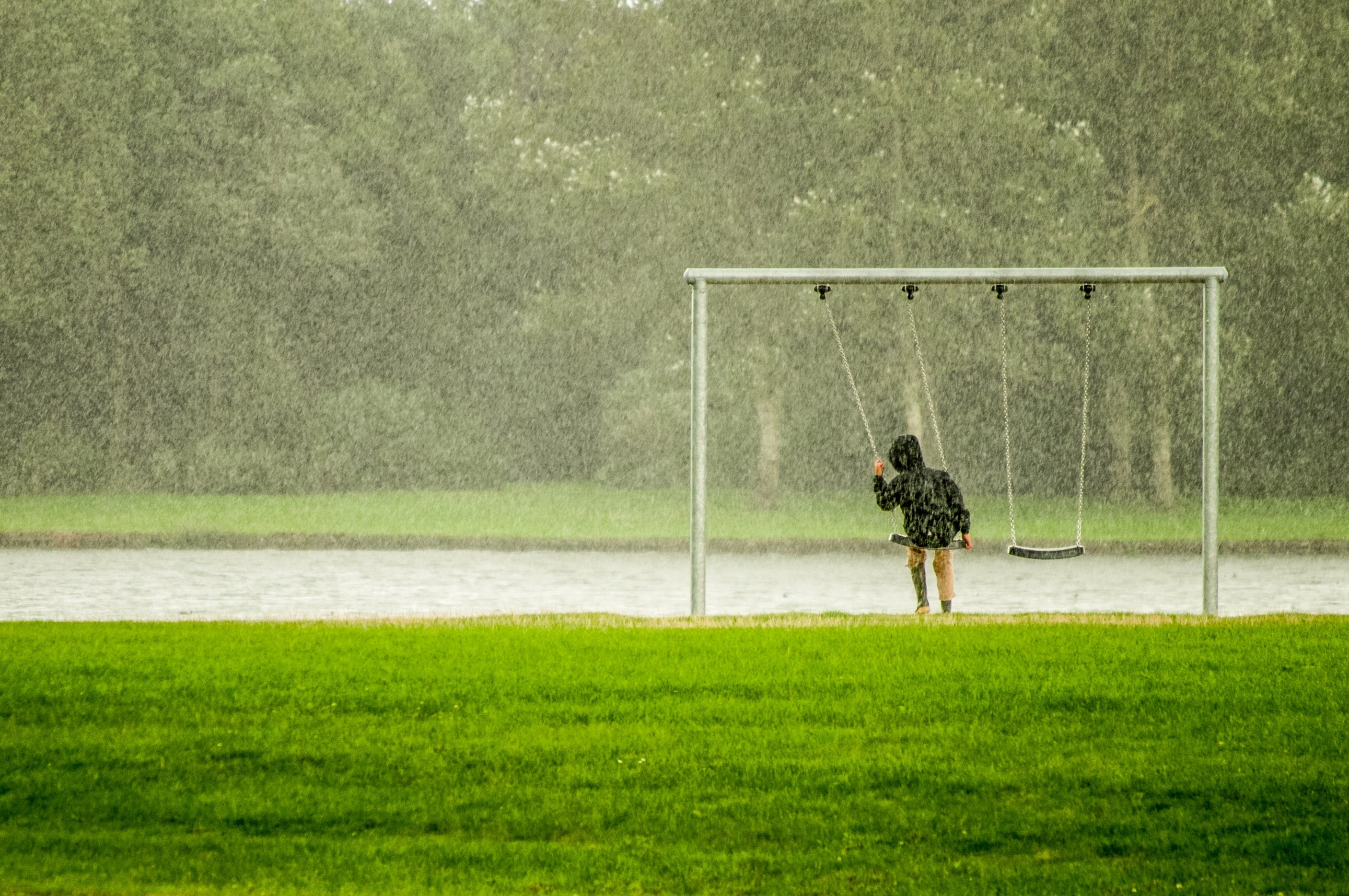 Criança brincando em balanço na chuva (Foto: Pexels)