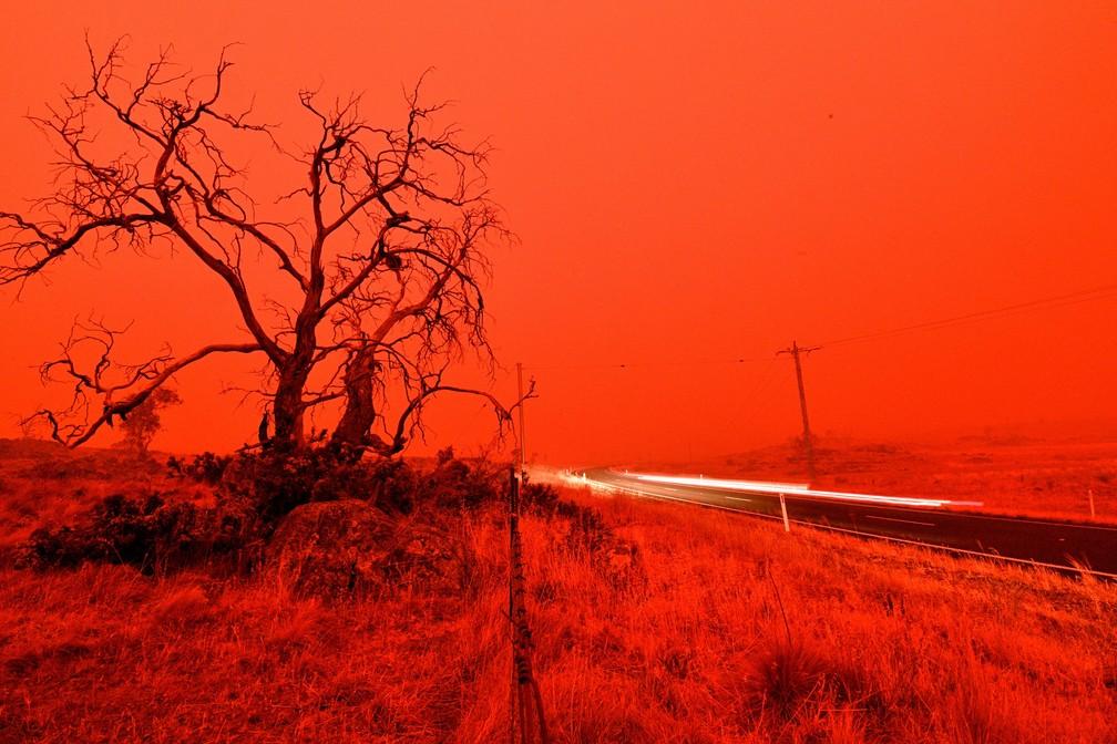 4 de janeiro  - Foto de longa exposição mostra um carro passando por uma estrada com o céu fica vermelho de fumaça do incêndio nos arredores de Cooma, na Austrália. Até 3 mil reservistas militares foram convocados para enfrentar a crise de incêndios no país  — Foto: Saeed Khan/AFP