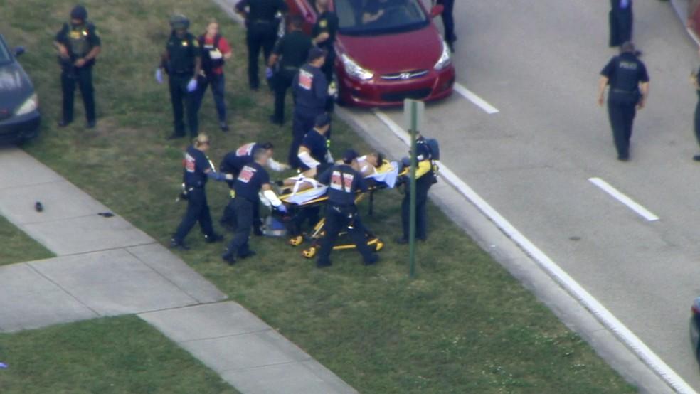 Ferido em tiroteio em escola em Parkland é transportado a embulância (Foto: WPLG-TV via AP)