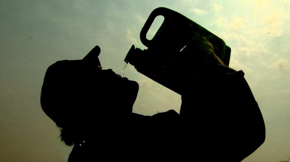Produtor rural toma água diante do sol escaldante em Ribeirão Preto (SP) — Foto: Reprodução/EPTV