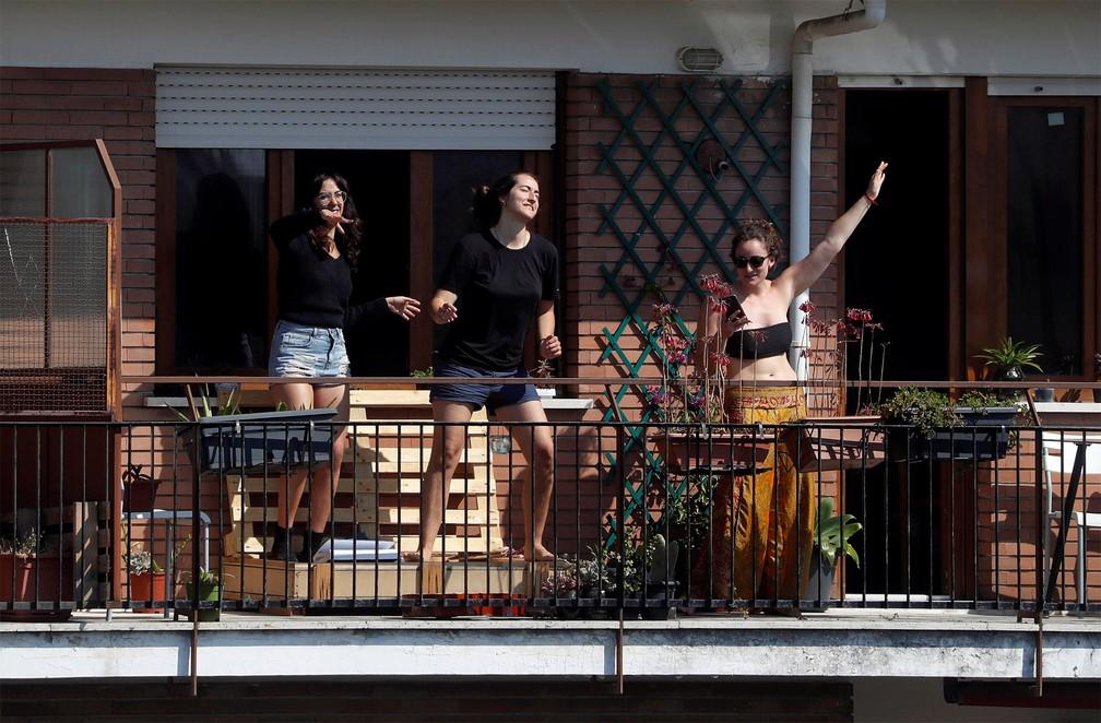 20 de março - Mulheres dançam em uma varanda de Roma, na Itália, respondendo ao chamado coletivo de flash mob feito por diversas rádios italianas em tempos de quarentena devido ao coronavírus. As rádios tocaram a mesma música e pediram que as pessoas dançassem em suas casas para promover a alegria — Foto: Yara Nardi/Reuters