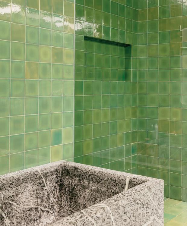 Para dar um toque pessoal, Andreia Varejão instalou azulejos portugueses no banheiro, os quais contrastam com a banheira de mármore (Foto: Stephan Ruiz/ Reprodução)