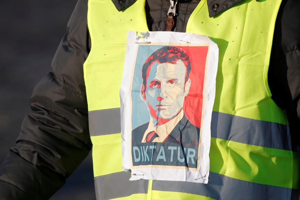 Manifestante dos 'coletes amarelos' exibe foto do presidente francês Emmanuel Macron durante protesto — Foto: Charles Platiau/Reuters