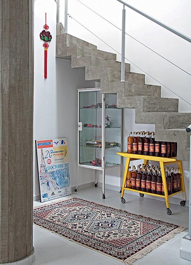 O canto embaixo da escada expõe a coleção dos moradores. O carrinho de chá retrô armazena as garrafas de cachaça envelhecida e o armário de farmácia guarda miniaturas de carros. Projeto da Casa 14  (Foto: Maíra Acayaba)