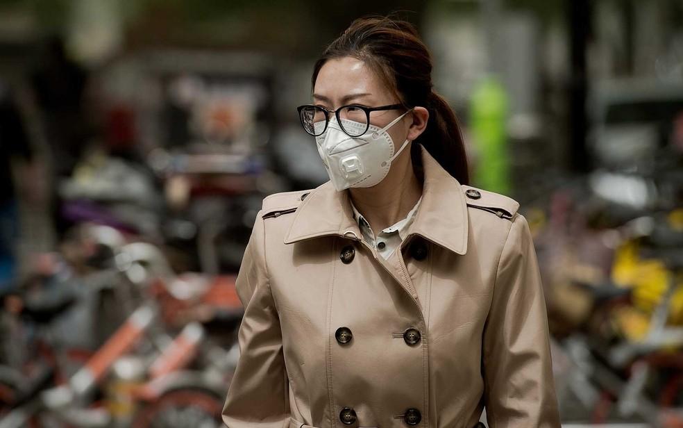 Mulher usa uma máscara contra poluição por partículas de areia em Pequim (Foto: Nicolas Asfouri / AFP Photo)