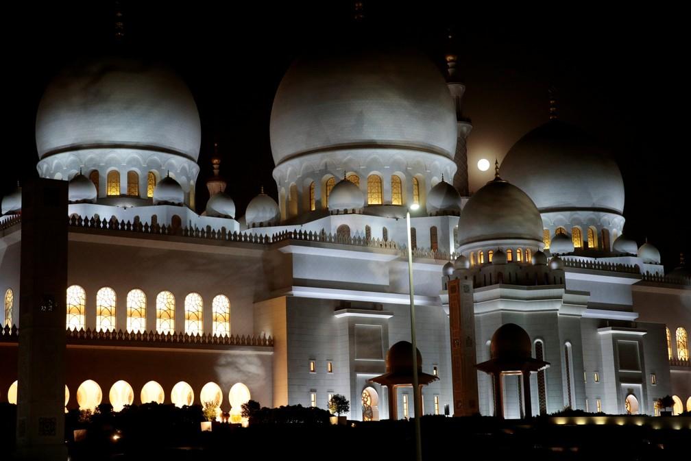 """ONDE ESTÁ A LUA? A foto de Christopher Pik, da Reuters, mostra o """"nascer"""" da Lua de Sangue perto da Grande Mesquita Sheikh Zayed. Ao contrário das imagens com grandes teleobjetivas, o satélite aparece em tamanho bem mais discreto. (Foto: Christopher Pik/Reuters)"""