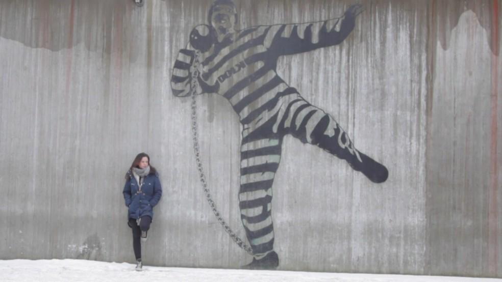 Linn Andreassen, guarda da prisão de Halden, na Noruega, ao lado de grafite no local — Foto: Reprodução/BBC