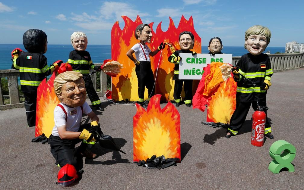 Ativistas usando cabeças gigantes representando os líderes do G7 posam como bombeiros para chamar atenção sobre luta contra desigualdade, na véspera da abertura do G7 em Biarritz, na sexta-feira (23) — Foto: Reuters/Regis Duvignau