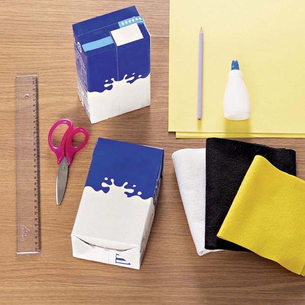 1. Material –  2 caixas de leite vazias  Régua  Tesoura  Lápis  Cola  Retalhos de feltro branco, amarelo e preto  Papel color plus amarelo A3. (Foto: Bruno Marçal / Editora Globo)