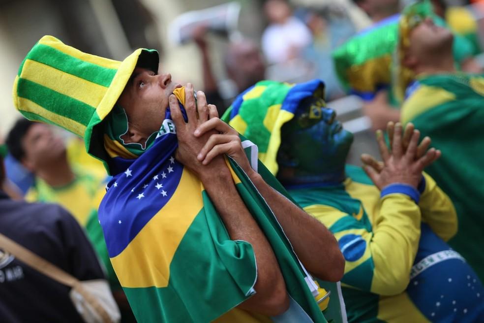 Torcedor concentrado se enrola em bandeira durante jogo do Brasil (Foto: Fábio Tito/G1)