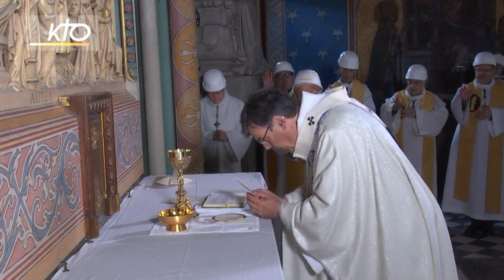 Único momento da missa na Catedral de Notre-Dame em que o arcepispo Michel Aupetit retirou o capacete foi durante o rito de consagração da hóstia e do vinho como o corpo e o sangue de Cristo — Foto: Reprodução/KTOTV