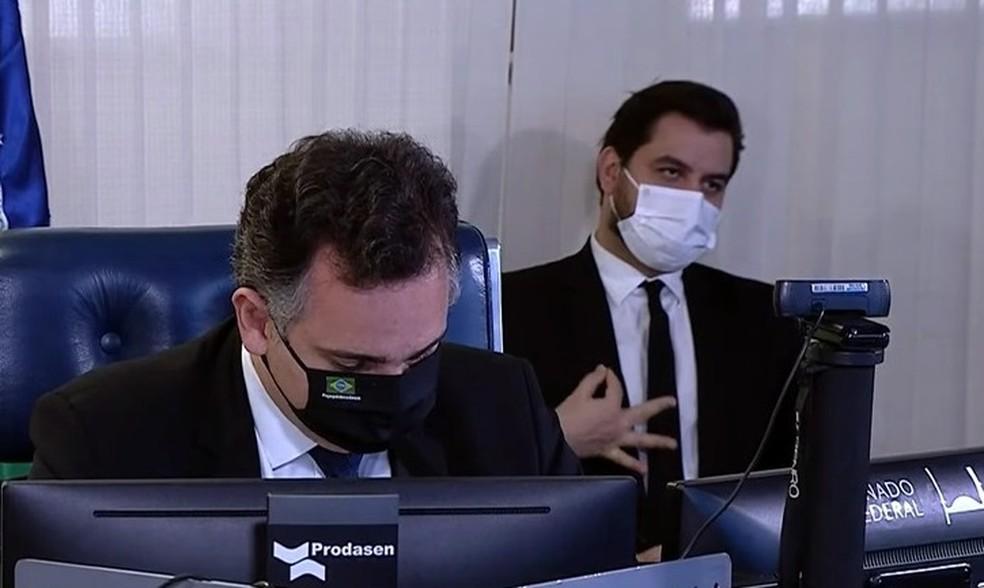 Assessor especial de Bolsonaro, Filipe Martins (ao fundo), faz gesto com a mão durante sessão do Senado no dia 24 de março de 2021.  — Foto: Reprodução/TV Senado