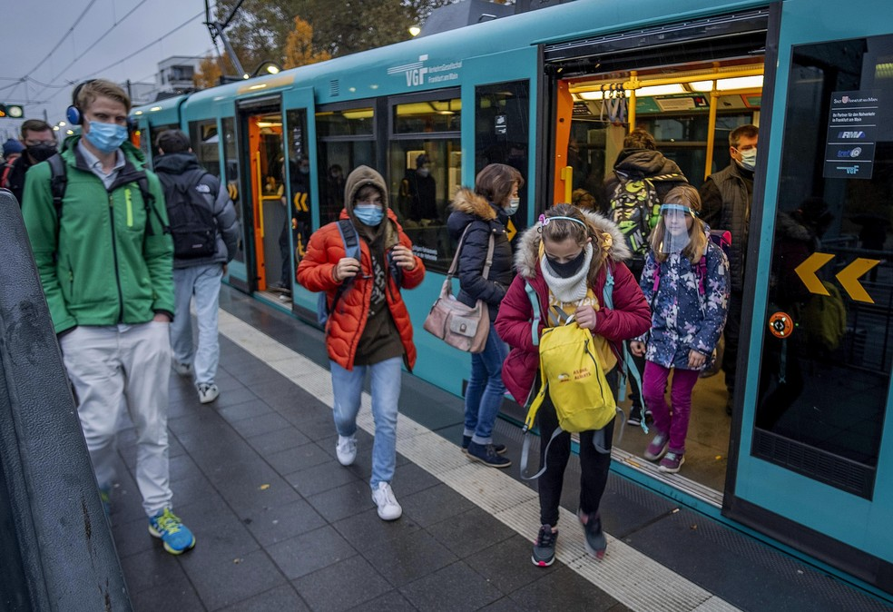 Estudantes com máscara de proteção deixam metrô em Frankfurt, na Alemanha, nesta quarta-feira (28) — Foto: Michael Probst/AP