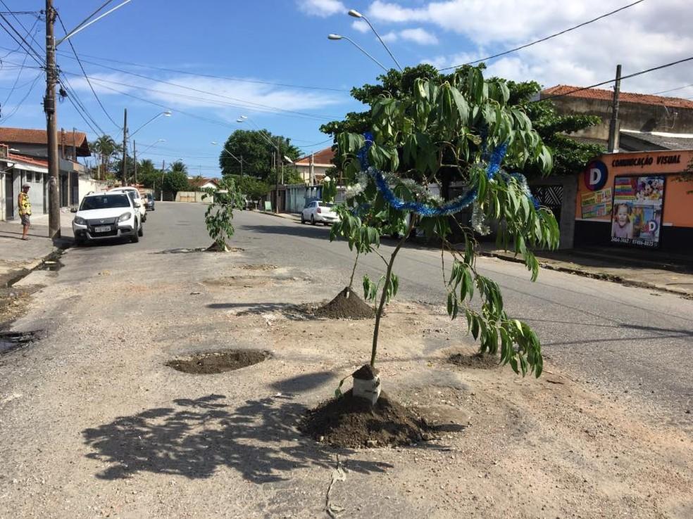 Moradores plantam 'pés de asfalto' em buracos de rua em São Vicente, SP — Foto: Divulgação/Facebook
