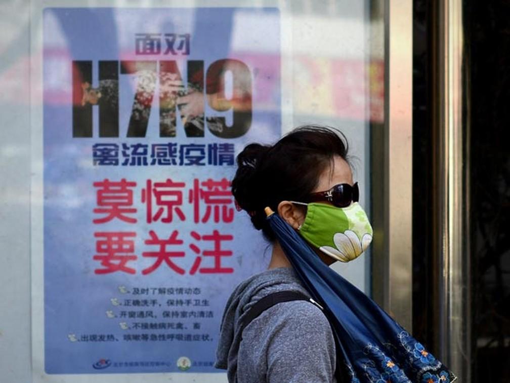 Usando máscara, mulher passa por cartaz com orientações contra a transmissão do vírus H7N9, em Pequim (Foto: Wang Zhao/AFP)