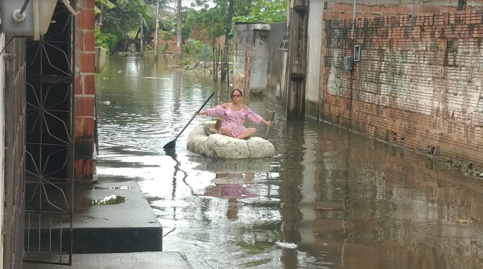 Dona de casa improvisa balsa para poder sair de casa em Fortaleza. — Foto: Halisson Ferreira/TV Verdes Mares