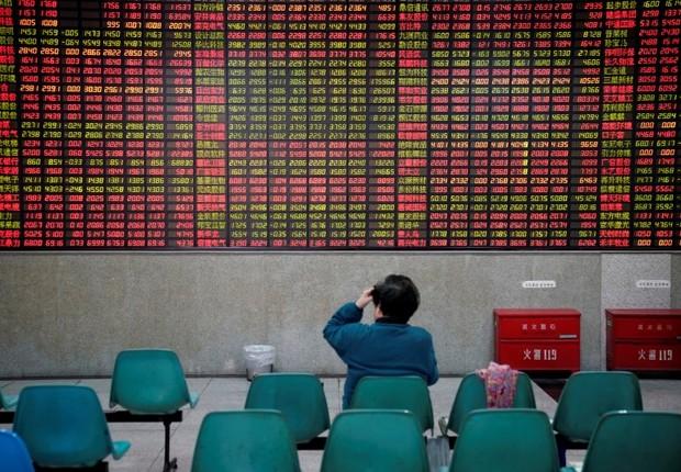 Investidor observa dados de ações em casa de corretagem em Xangai, na China - bolsa - ações - Ásia (Foto: Aly Song/Reuters)