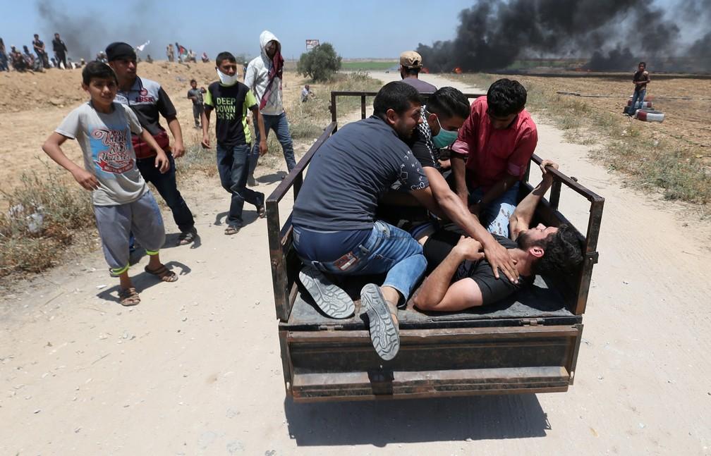 Um palestino ferido é retirado por outros durante um confronto com tropas israelenses após protestos na fronteira entre Gaza e Israel contra a inauguração da embaixada dos EUA em Jerusalém (Foto: Ibraheem Abu Mustafa/Reuters)