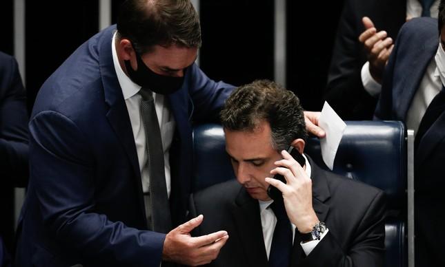 Flávio Bolsonaro passa o telefone para o novo presidente do Senado, Rodrigo Pacheco