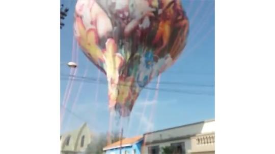 Balão fica enroscado entre casas e fios da rede elétrica em Atibaia; assista