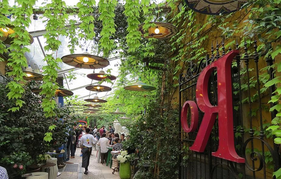 Recheado de plantas, o pátio de entrada do Spazio Rossana Orlandi está sempre cheio de visitantes. Penduradas na estrutura de vidro, luminárias da marca PetLamp