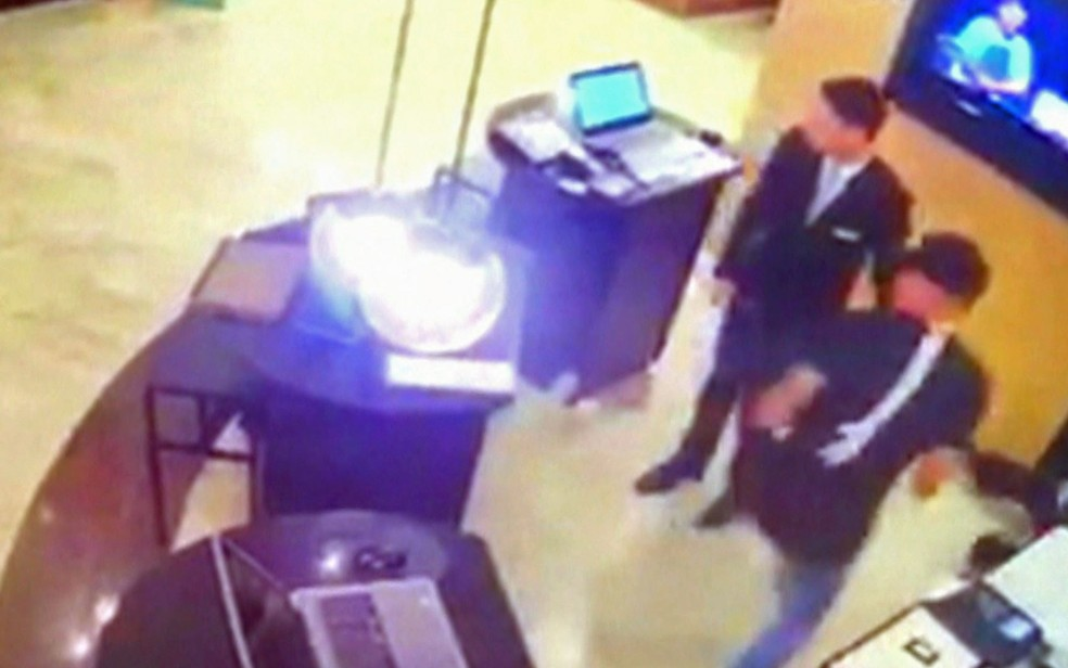Funcionários do hotel correm para se abrigar ao ouvir os tiros (Foto: TV Globo/Reprodução)
