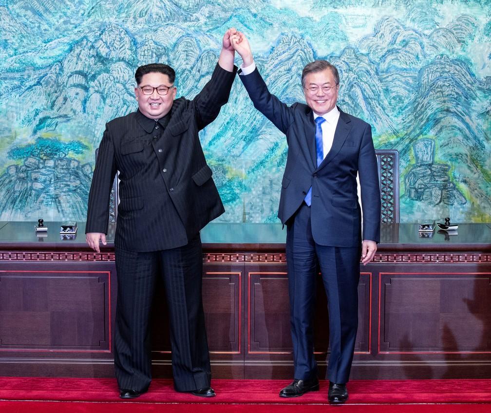 O presidente sul-coreano Moon Jae-in e o líder da Coreia do Norte Kim Jong-un erguem as mãos juntas durante encontro em abril na zona desmilitarizada que separa os dois países (Foto: Korea Summit Press Pool/via Reuters)