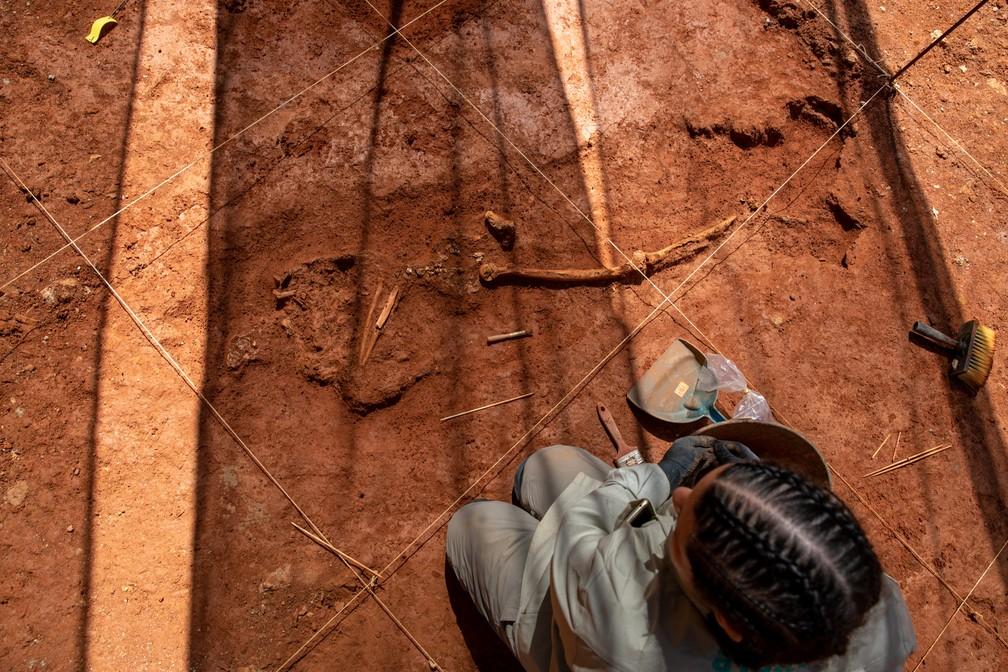 Arqueóloga trabalha na escavação em um sítio funerário descoberto em um terreno na Liberdade, em São Paulo. A região abrigava o Cemitério dos Aflitos, o primeiro cemitério público da cidade, onde escravos, condenados e outras pessoas marginalizadas eram enterradas — Foto: Marcelo Brandt/G1
