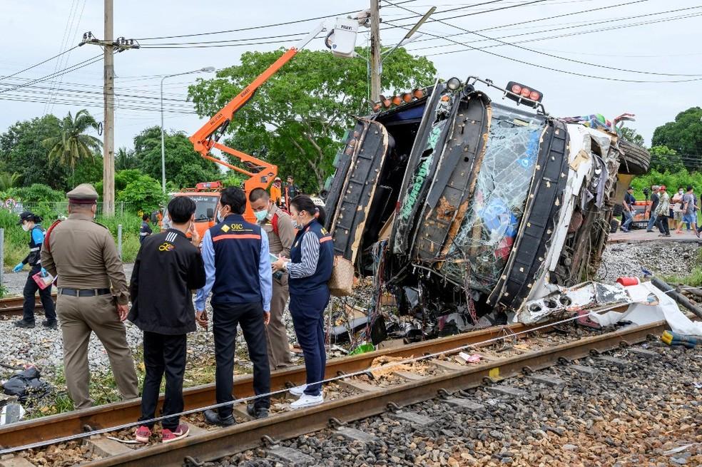 11 de outubro - Os investigadores trabalham com os destroços de um ônibus que capotou após ser atingido por um trem perto da estação ferroviária Khlong Kwaeng Klan, na província de Chachoengsao, a leste da capital tailandesa, Bangkok. — Foto: Mladen Antonov / AFP