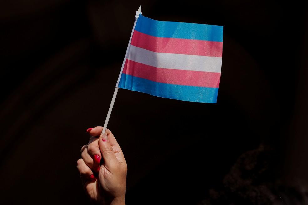 Uma pessoa segura bandeira do movimento trans — Foto: Brendan McDermid/Reuters/Arquivo