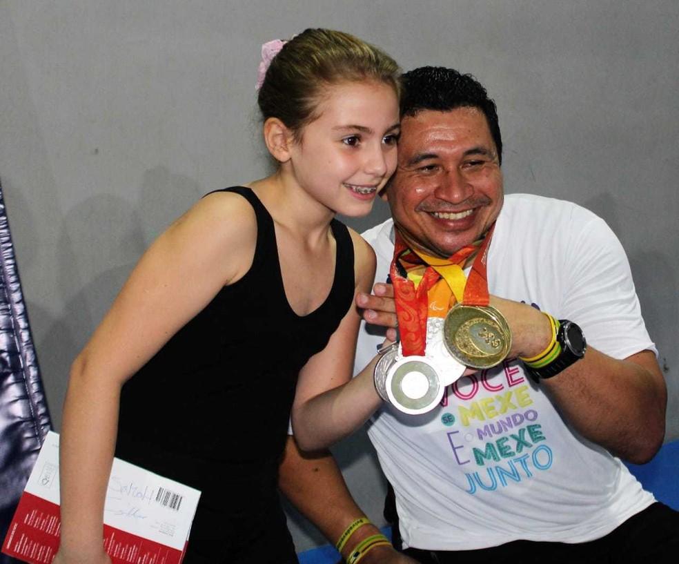 Clodoaldo Silva posa para foto com uma fã mirim, admirada pelas medalhas do ex-nadador   — Foto: Arquivo Pessoal