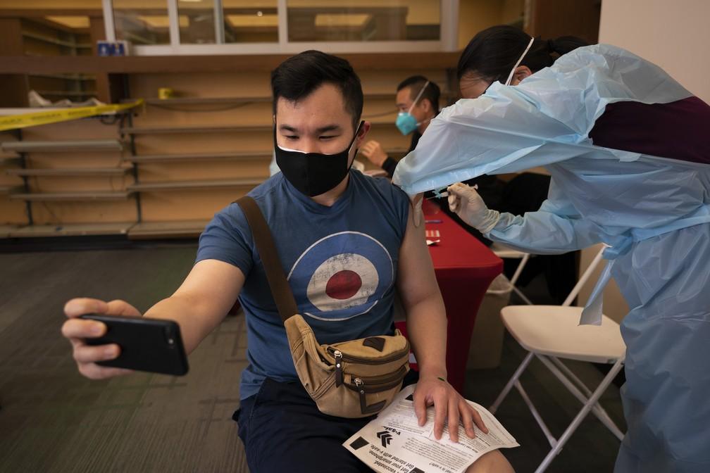 Freeson Wong, de 31 anos, tira selfie enquanto recebe uma dose da vacina contra Covid-19 da Moderna, em 12 de abril de 2021, no bairro de Chinatown de Los Angeles — Foto: Jae C. Hong/AP