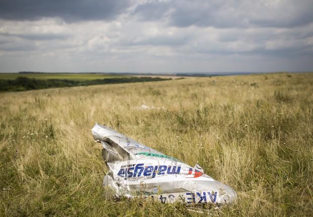 Destroços do voo MH17 da companhia aérea Malaysia Airlines são vistos em um campo de Grabovo, na Ucrânia. O avião fazia a rota de Amsterdam a Kuala Lumpur e transportava 298 pessoas a bordo (Foto: Rob Stothard/Getty Images)