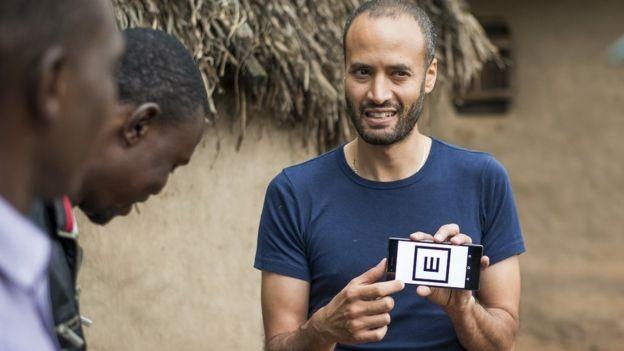 Andrew Bastawrous faz uma demonstração do aplicativo Peek Acuity para sua equipe no Quênia  (Foto: Rolex Joan Bardeletti/via BBC News Brasil)