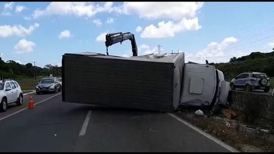 Caminhão tem pneu furado, perde controle, bate em carreta e tomba na BR-232
