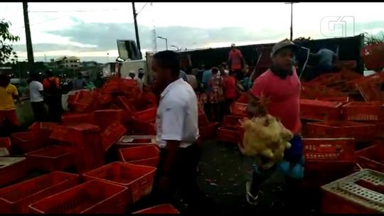 Caminhão com galinhas tomba e carga é levada; veja vídeo