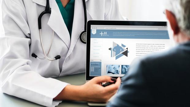 Médica exibe informações a paciente no notebook (Foto: Pexels)
