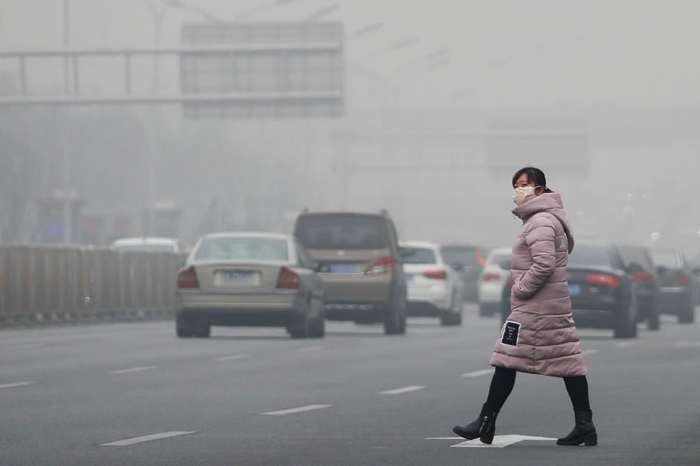 Mulher atravessa via movimentada em Pequim, na China, usando máscara para se proteger da poluição em janeiro de 2017 (Foto: AP Photo/Andy Wong)