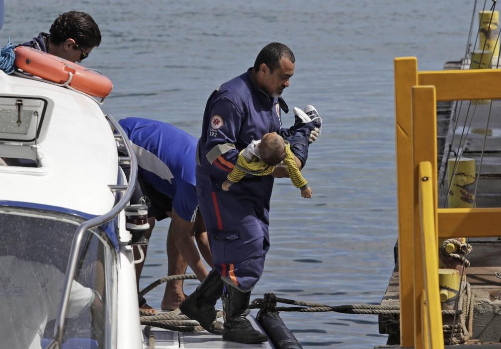 Socorrista do Samu leva um bebê no colo após uma embarcação naufragar em Mar Grande, na Baía de Todos os Santos, na Bahia (Foto: Xando Pereira/Agência A Tarde/Estadão Conteúdo)